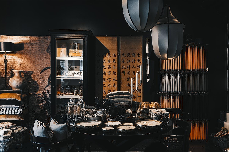 uppdukat matsalsbord vid vägg med stora tavlor och skåp i butiken Atelier 42 i Trollhättan