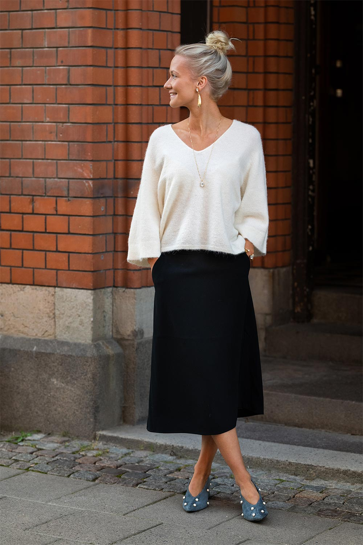 Ida i vit stickad tröja och svart kjol framför port