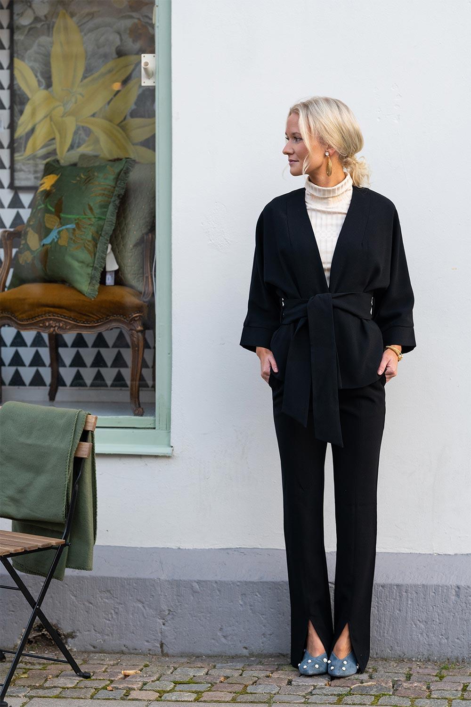 Ida iklädd kostym från Stylein framför entrén till butiken Atelier 42 i Trollhättan