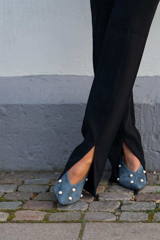 Ida i blå mockaskor med pärlor på kullerstensgata