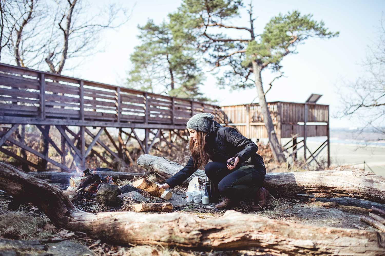 Johanna lägger på en vedkubbe på brasan vid utkiksplatsen på Hunneberg