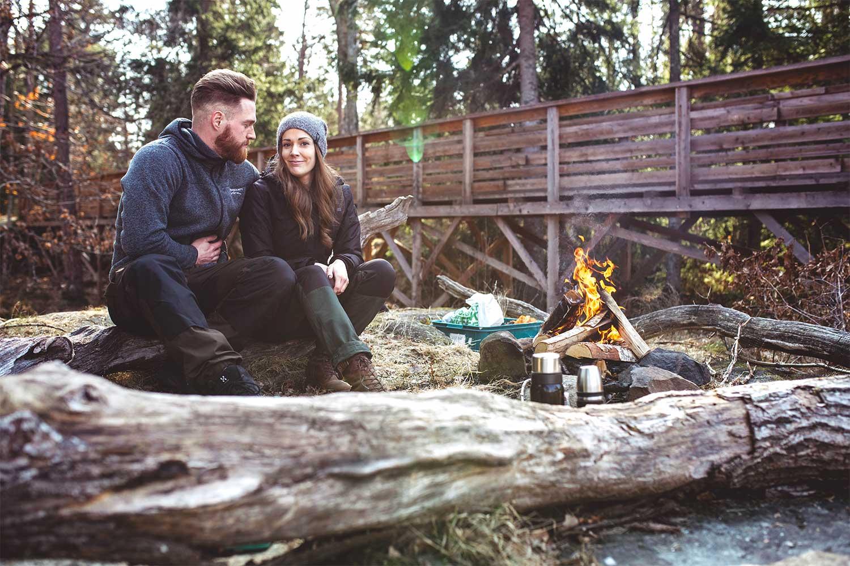 Per och Johanna sitter på en stock vid brasan på Hunneberg