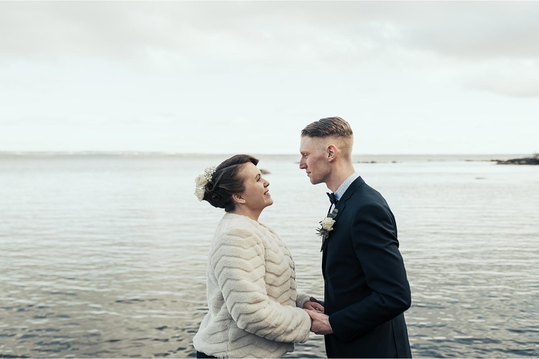 brudpar som håller händer och ser varandra i ögonen framför sjö