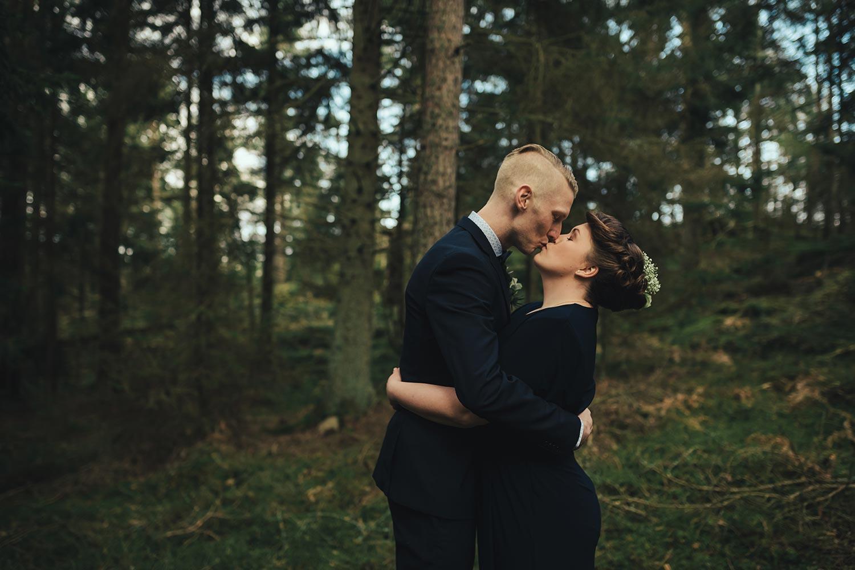 kyssande brudpar i skogen