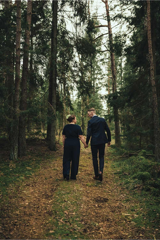 brudpar som promenerar bortåt i skogen